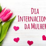 Women's day card with Portuguese words 'dia internacional da mulher'. Tulip flower small hearts on white wooden background.